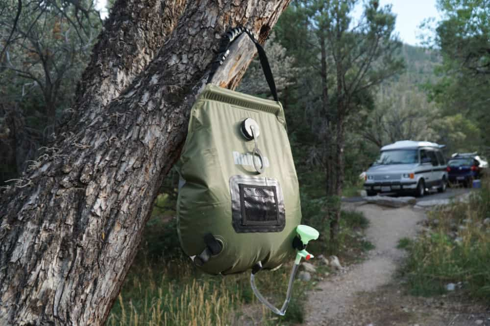 Solar shower hanging in a tree in a campsite, a van life gear essential