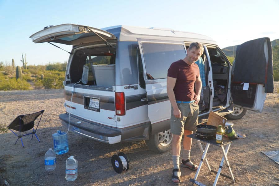 Man standing next to boondocking gear and Chevy Astro van