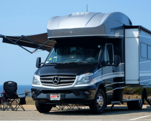 Class C RV Rental parked at the beach with lounge chairs nearbh
