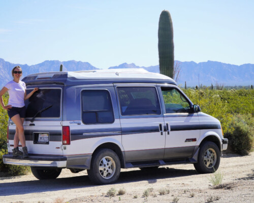 Chevy Astro van camper in the desert with woman on back bumper