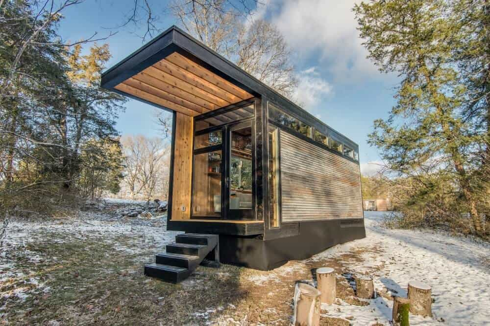 Cornelia Tiny House for Sale with a large awning parked in the forest