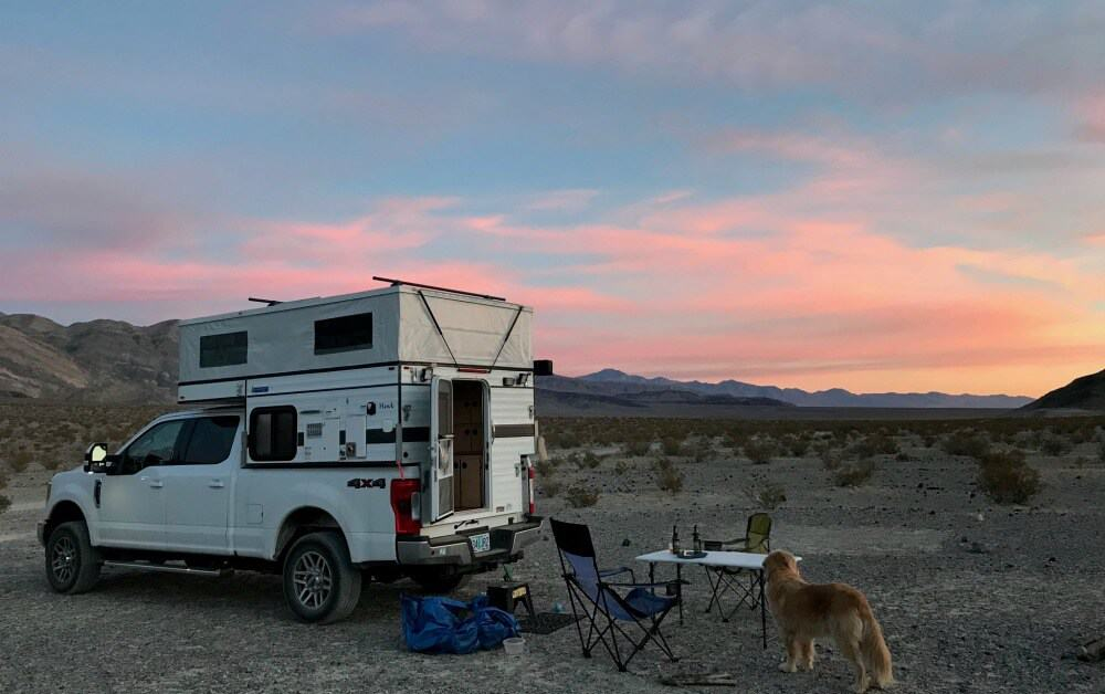 Four Wheel Truck camper with camping chairs, a dog and a view