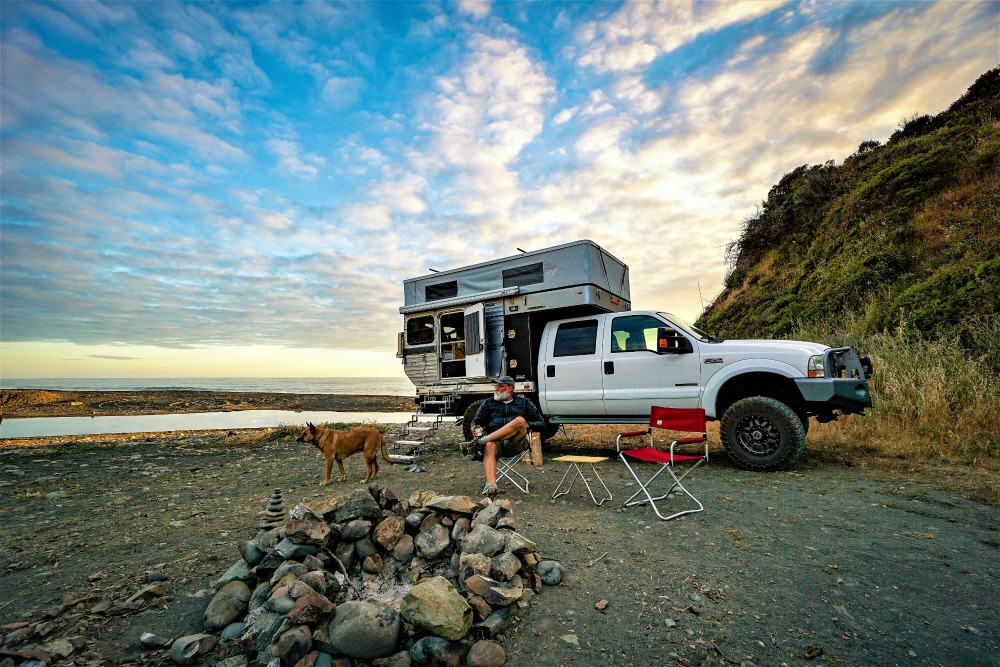 A pop up truck camper by Four Wheel Campers parked on the beach