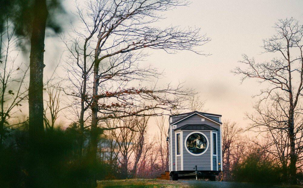 Monacle Tiny Home for Sale by Wind River has a huge round window out front, parked in a forest clearing