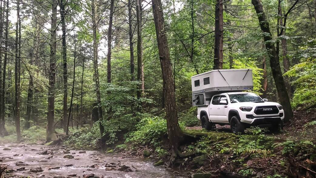 Swift Pop Up Camper by Four Wheel Campers driving down a forest road