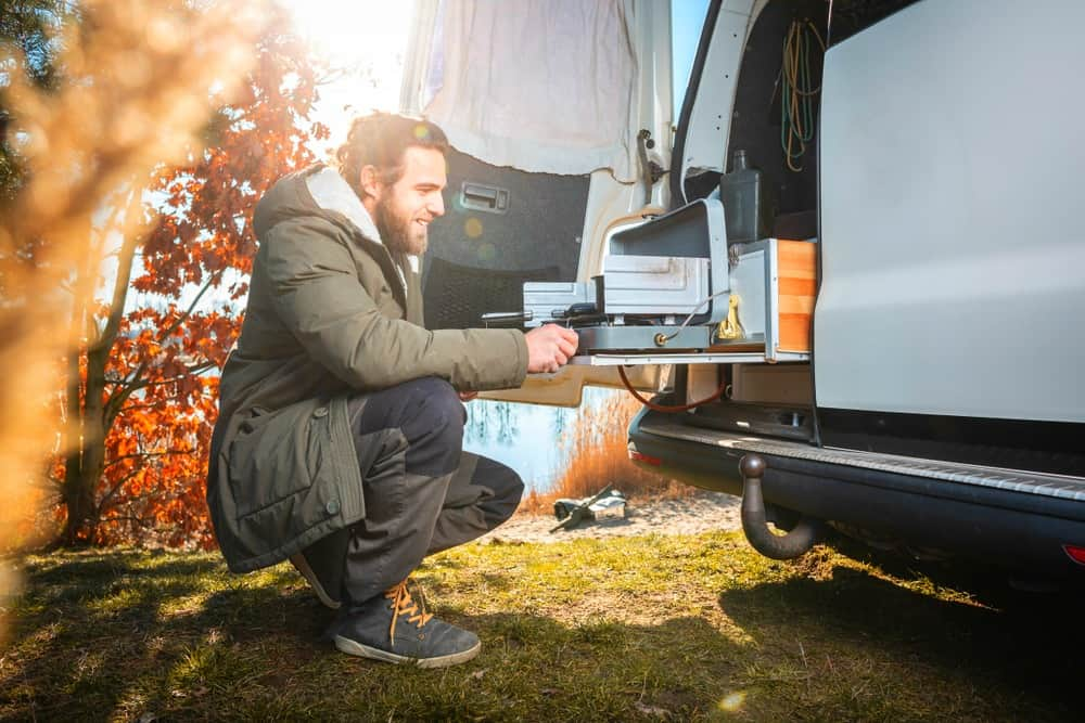 Man cooking on a camping stove right outside his campervan