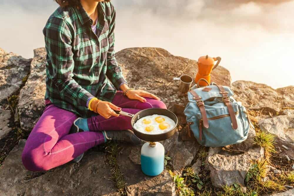 Young woman cooks eggs in a small camping stove overlooking a gorge