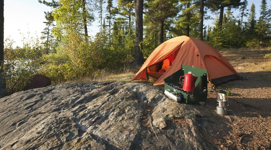 Portable Camping Stove set up on a rock outside a tent in the woods