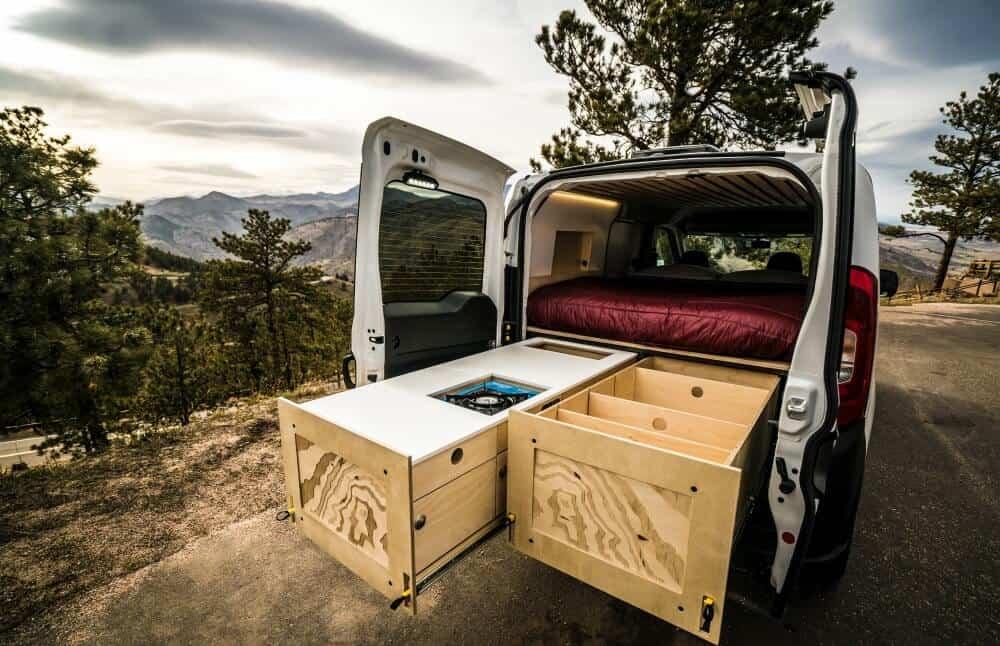 Cargo Van camper with a double slide that serves as a cooking area and storage.
