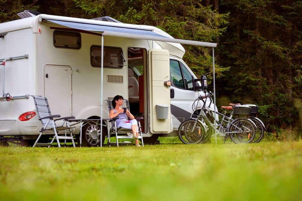 Woman sipping a drink in front of her RV