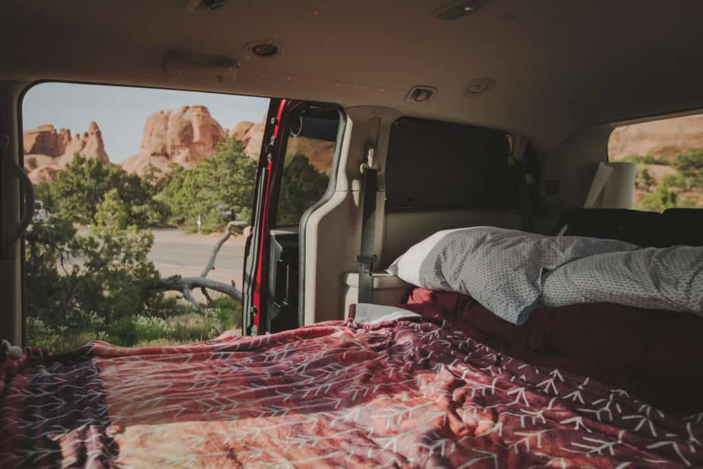 A minivan with a bed and the side door open is a perfect vehicle for stealth camping