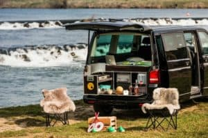 Van parked by the water with the hatch open showing the QuQuQ camper kit