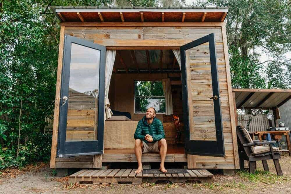 Rob Greenfield sits inside his 100-square foot tiny house