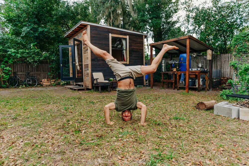 Rob Greenfield doing a headstand in front of his tiny house, which only cost $1,500