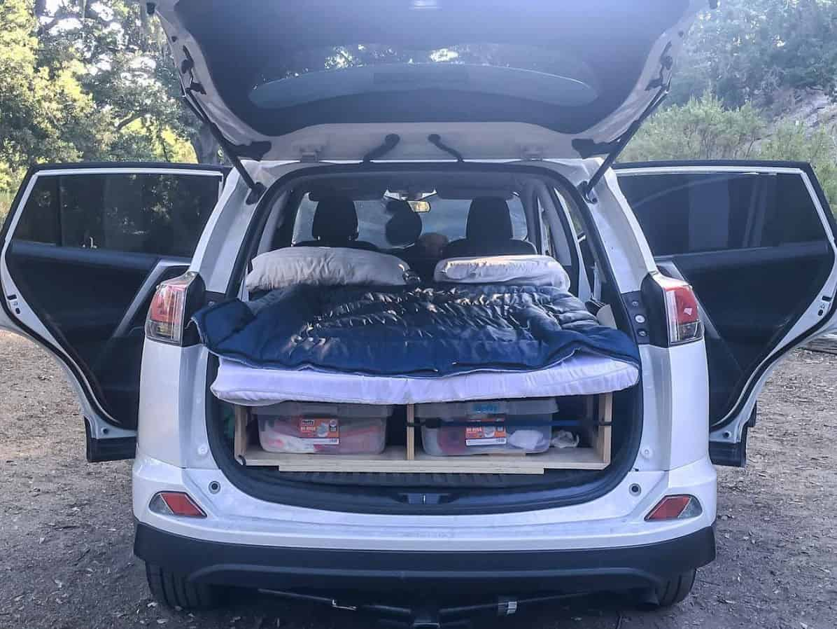The hatch opened on a Toyota Rav 4 SUV camper showing bed and storage