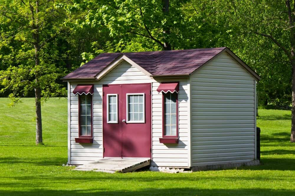 Red and cream shed tiny house on a bright green lawn