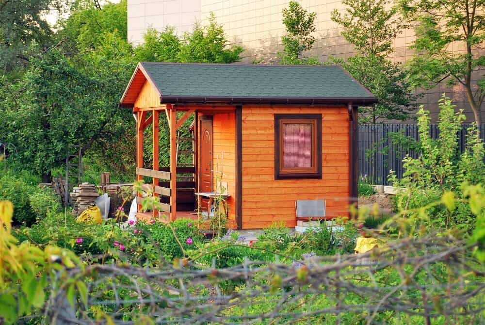 Tiny Wooden tiny house shed with a front porch