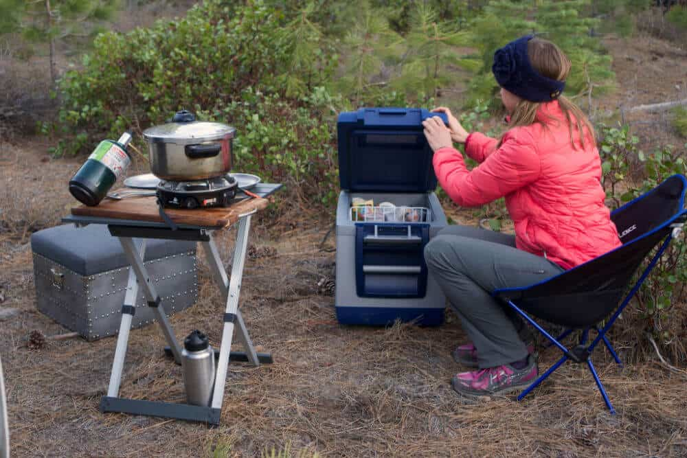 Woman opening an ARB 12 volt refrigerator in the forest