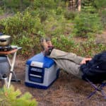 Man in a campsite with his feet propped up on an ARB portable refrigerator