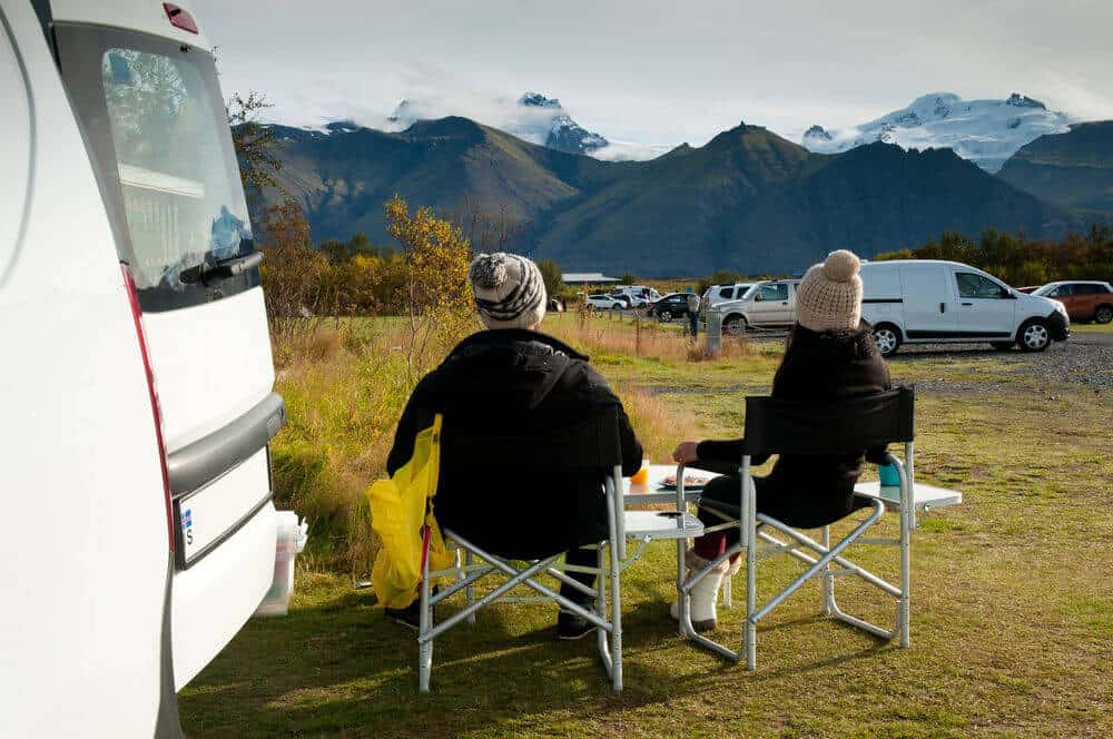 couple sitting at a folding camping table near their campervan