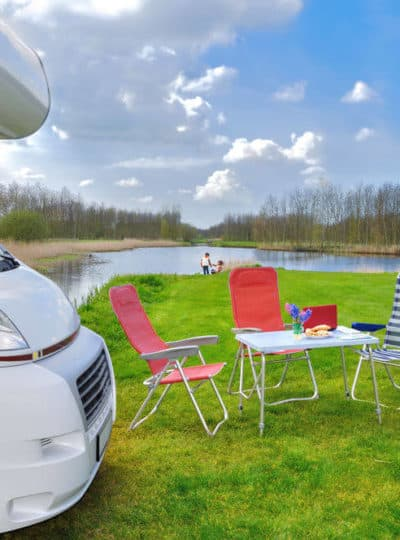 RV and a camping table with bright chairs on a lawn