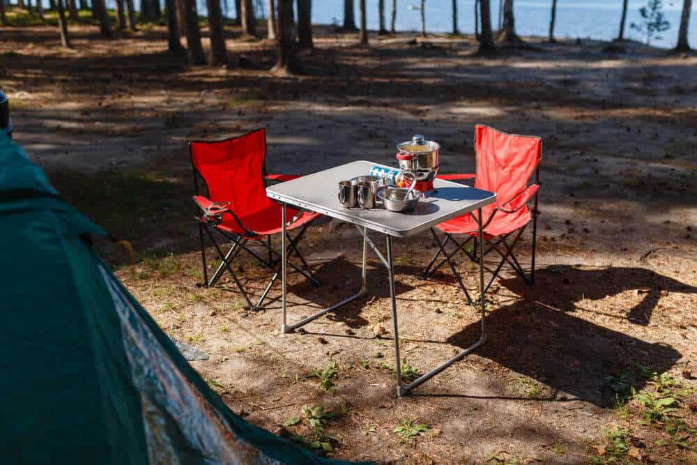 A compact RV folding table set up near a tent in the woods