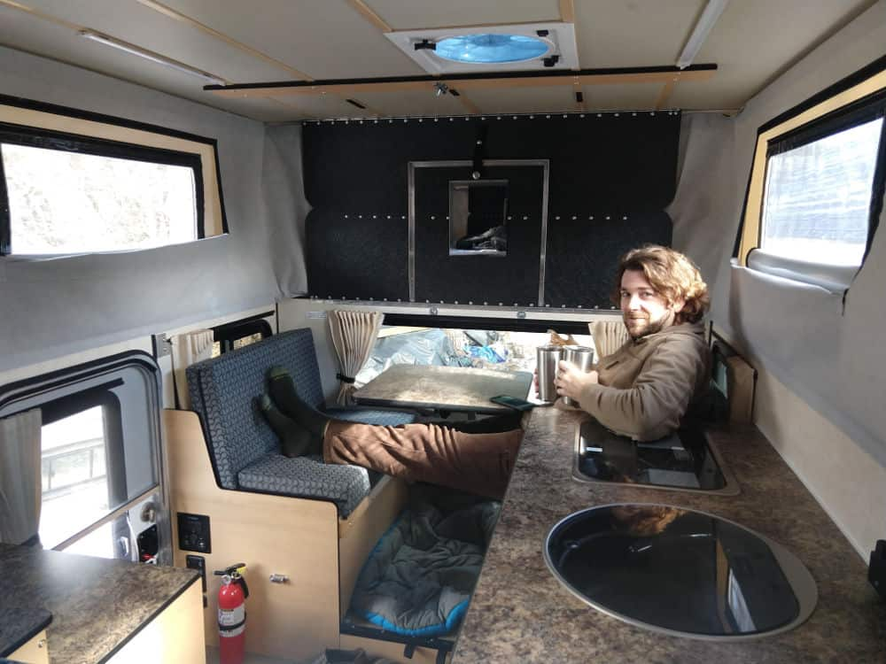 Adam relaxes in the back of the pop up truck camper by Four Wheel Campers