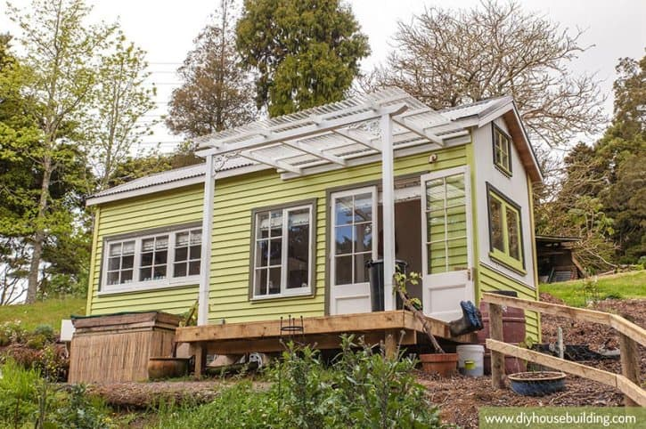 The bright yellow Lucy tiny house on wheels parked on a hillside