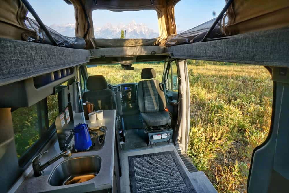 An interior view of a Sportsmobile Sprinter in the Wyoming mountains