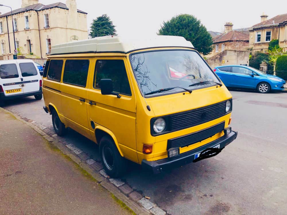 Little yellow van parked on the side of the road