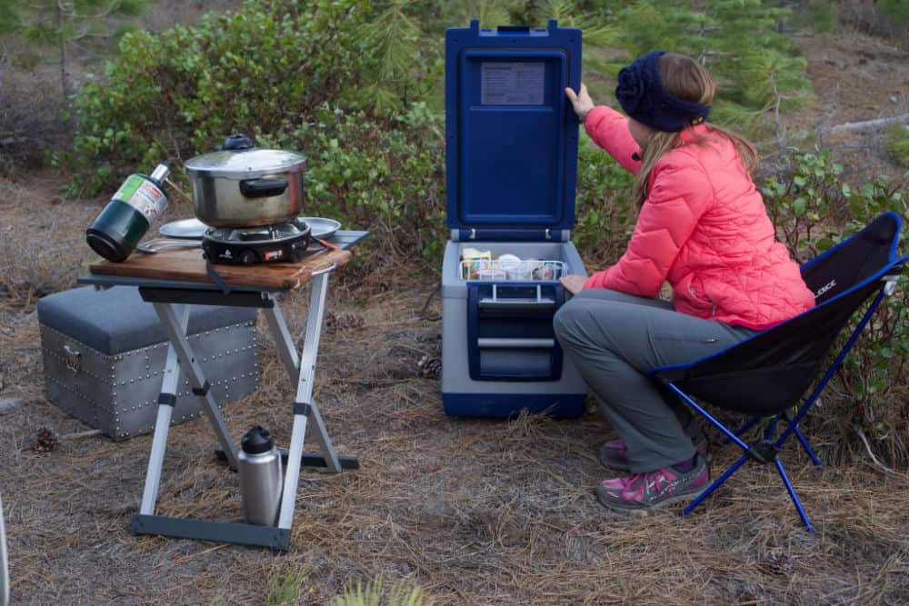 Woman looking in a 12-volt fridge while camping with a chair and camping table