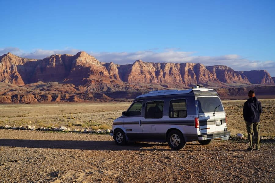 man standing next to van boondocking in Vermillion cliffs