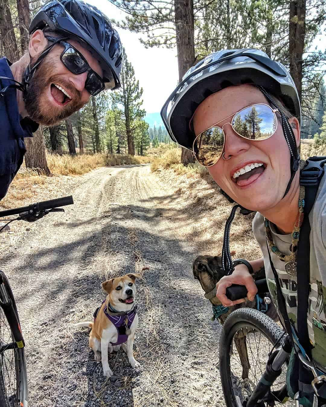 John and Jayme riding their bikes on a country road with their dog