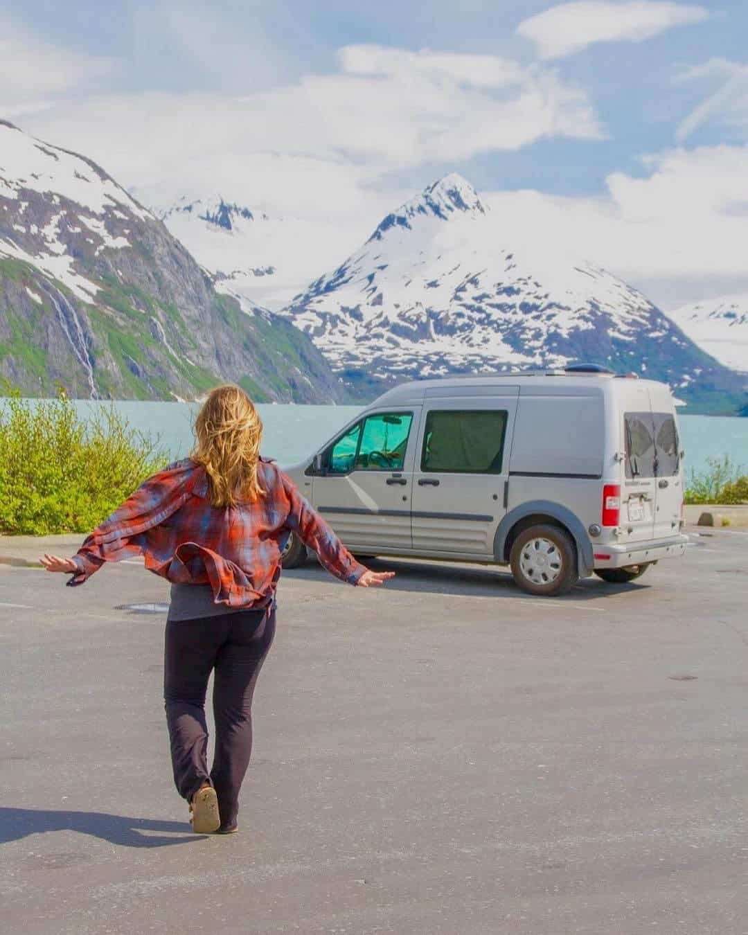 Girl running toward her Ford Transit Connect camper
