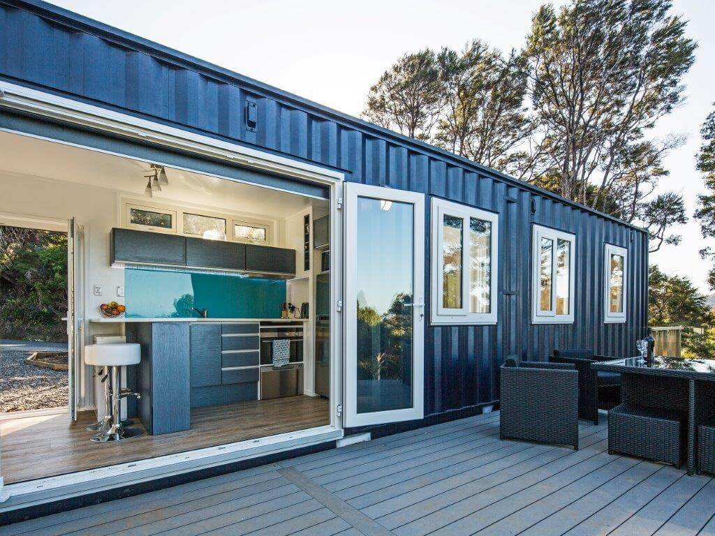 Large doors open into this shipping container home by IQ container homes