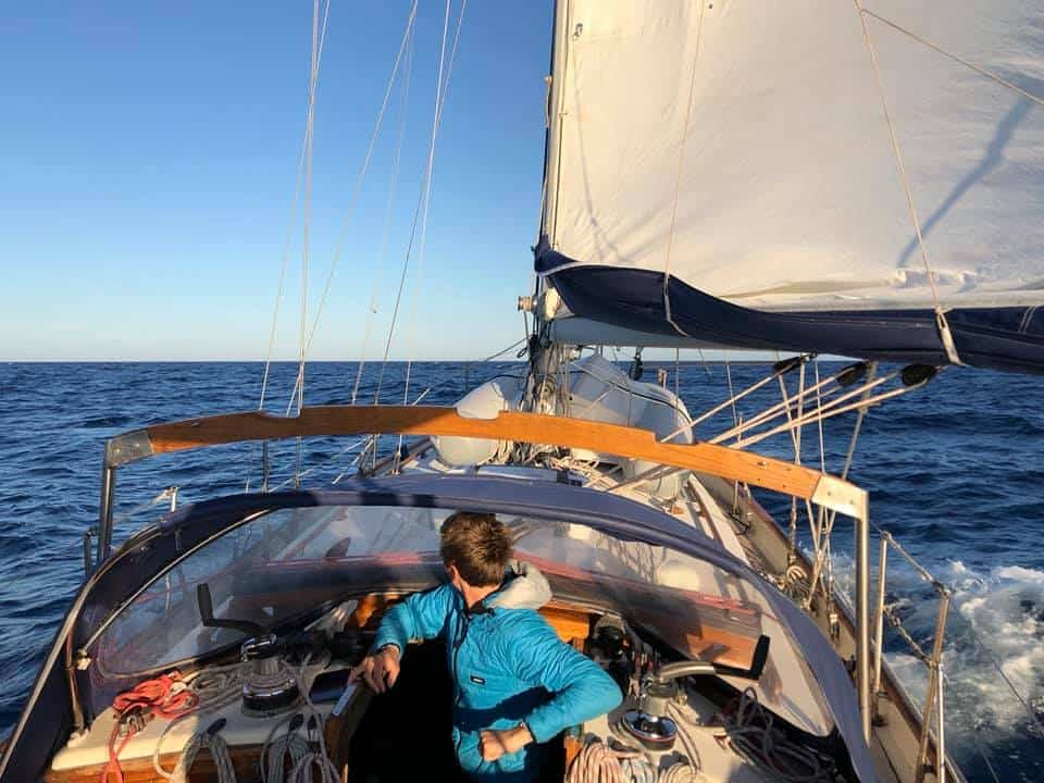 Elena and Ryan sailing their small cruising sailboat, a Tayana 37