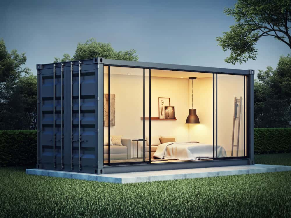 A shipping container home with a glass wall looking outside.