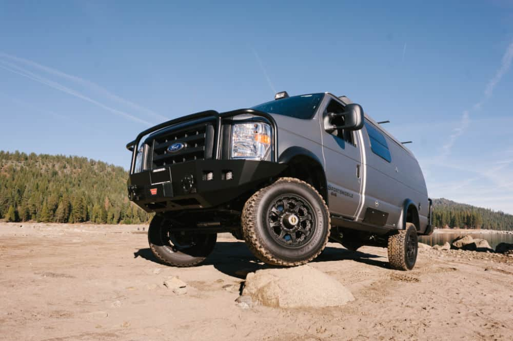 Sportsmobile 4x4 camper van parked on rocks in the high desert and forest