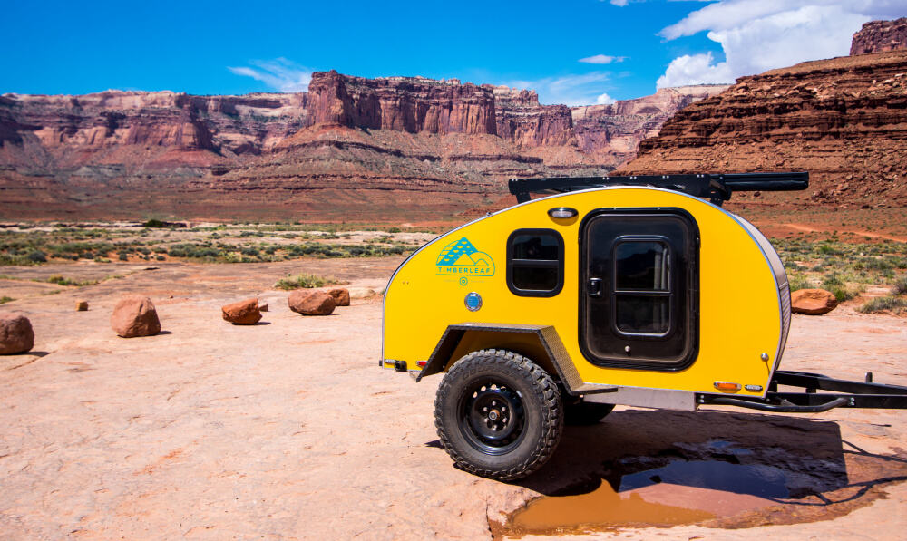 The bright yellow Pika Teardrop Camper in the desert