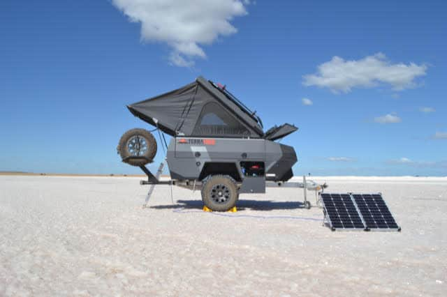 TerraTrek Off Grid Camper parked in the desert with solar panels on the ground.
