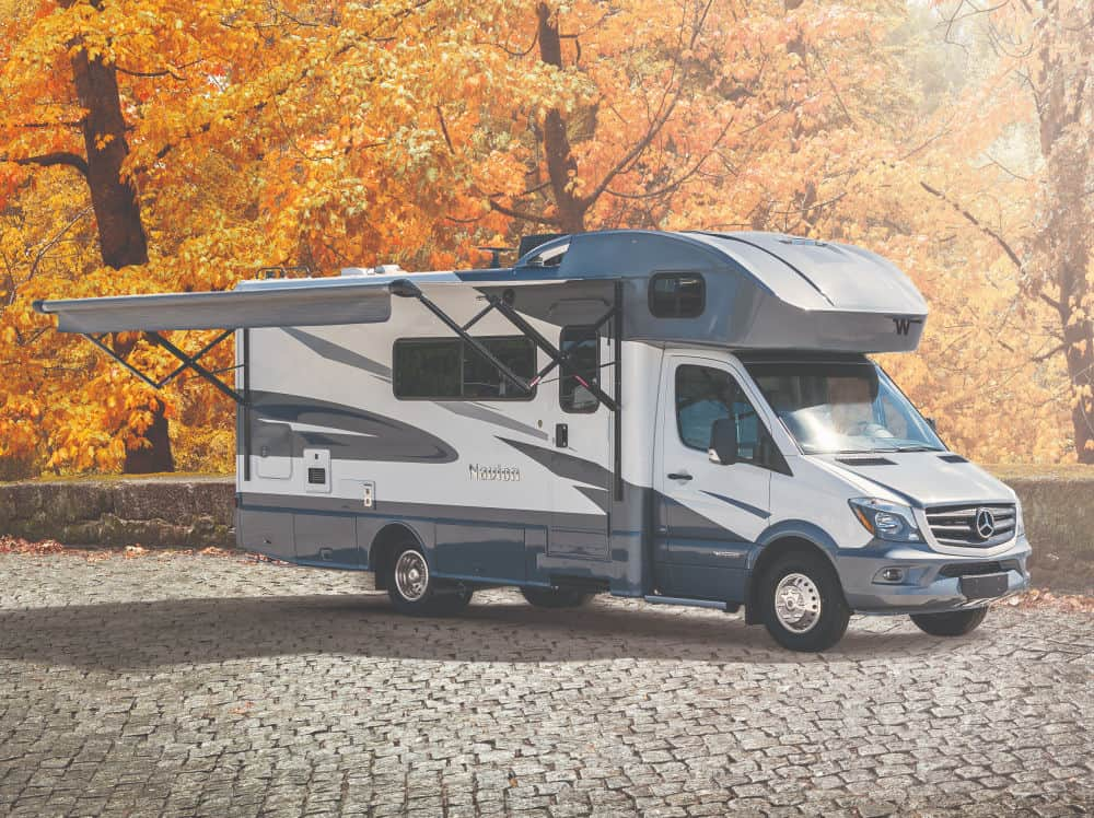 The Winnebago Navion small RV parked by fall foliage