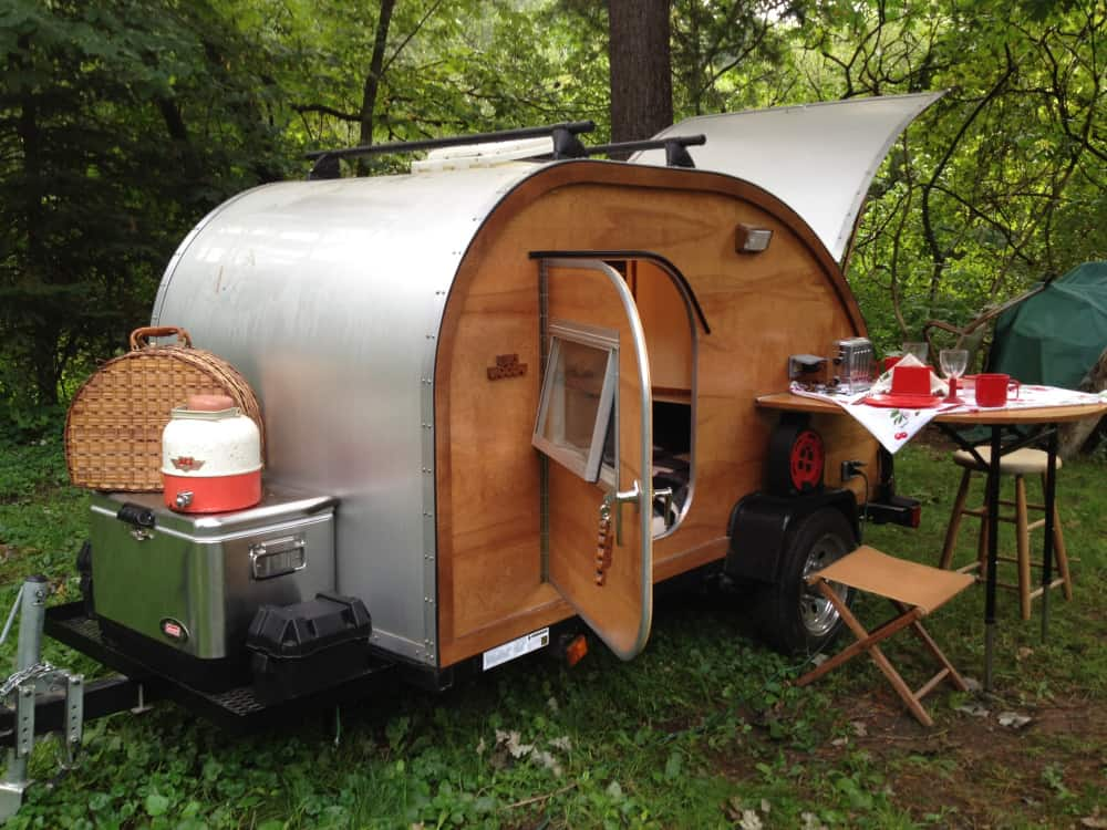 A beautiful wood teardrop camper in the forest