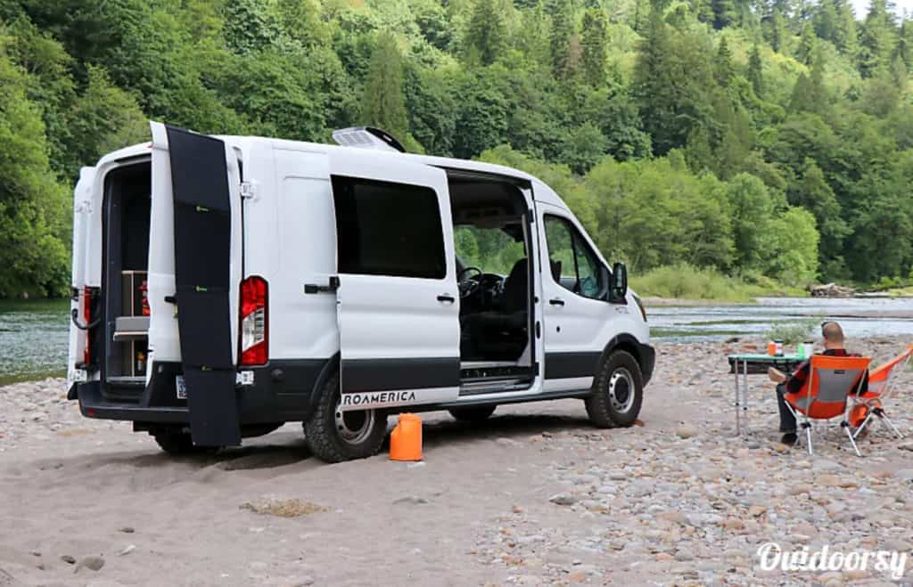 Ford Transit camper van parked near a river with a man sitting in a chair nearby