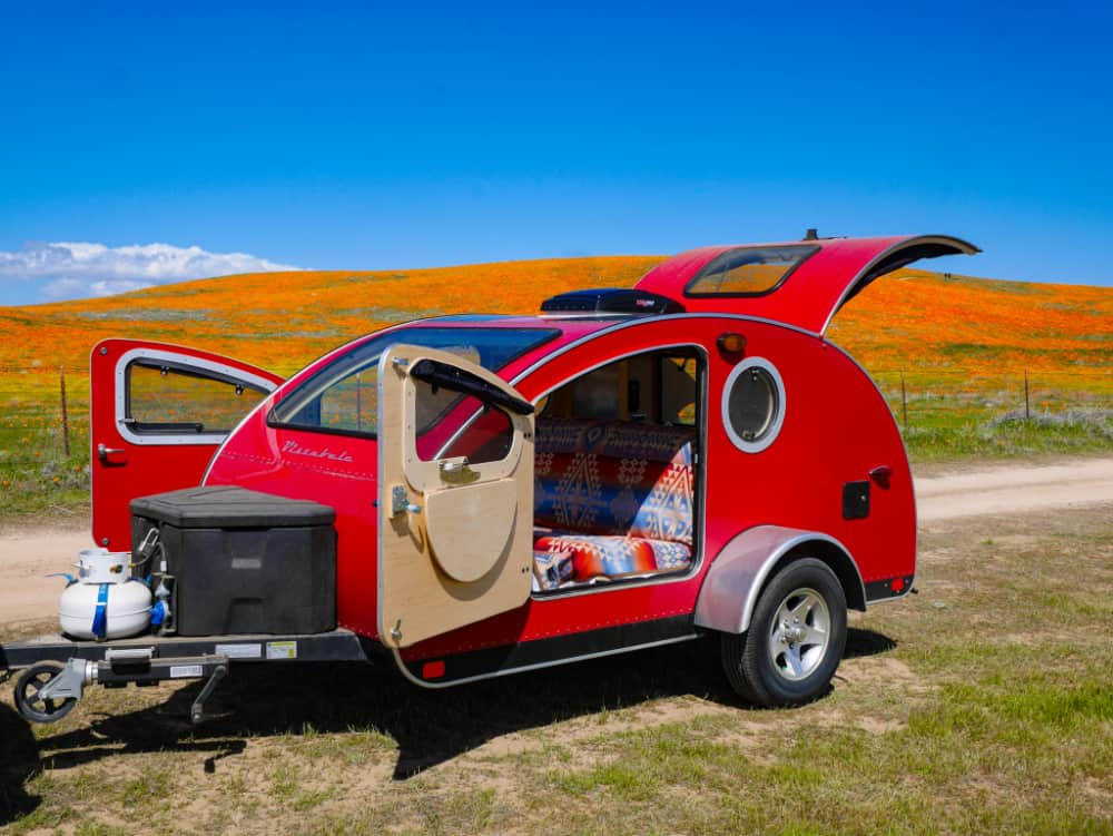 Bright red vistabule teardrop trailer with hatches and doors open