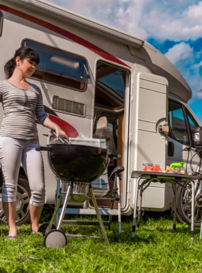 woman cooking on one of the best portable RV grills