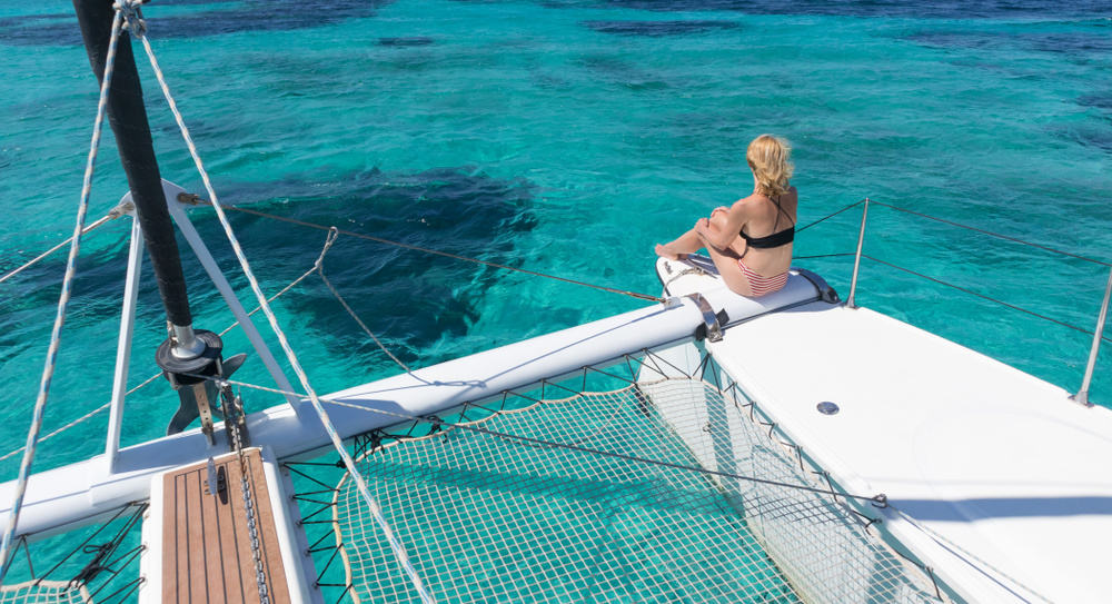 Woman sitting on the bow of a catamaran sailboat