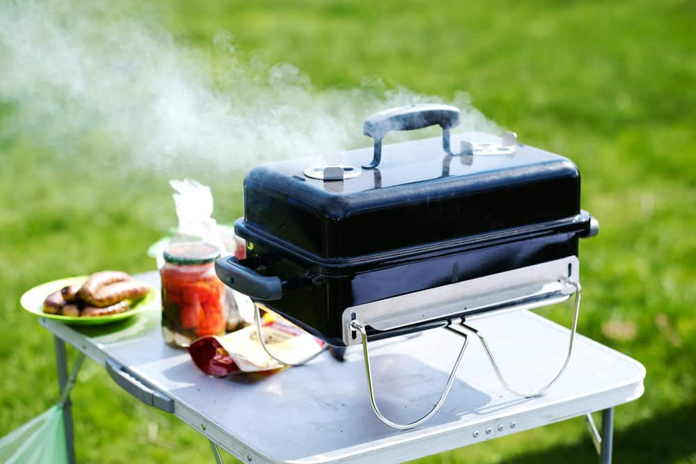 charcoal grill smoking on a camping table, one of the best RV grills