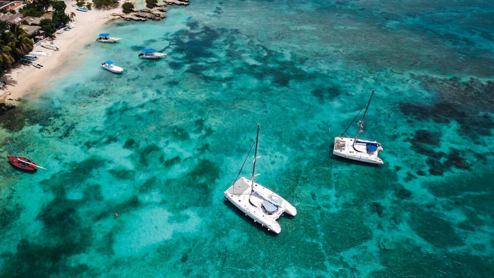 two catamarans anchored in a turquoise sea