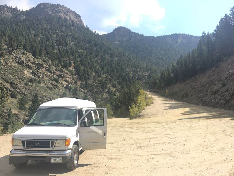 White Ford Econoline DIY camper parked on a dirt road