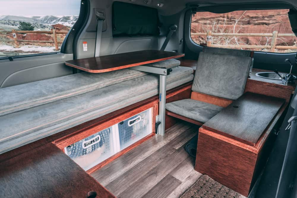 The folding bed and chair inside the Oasis Toyota Sienna camper